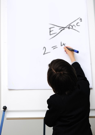 theory of relativity: Genius little boy writting E=mc2 on the board, new formula instead, conceptual idea
