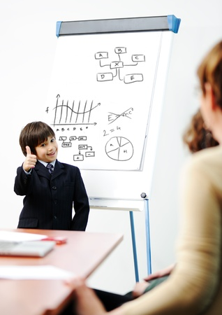 Genius kid on business presentation speaking to adults and giving them a lecture photo