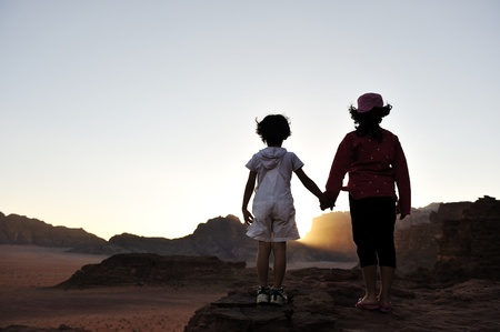 Waiting for the sunset in desert, brother and sister together visiting Africa. Boy and girl photo