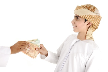 Arabic people, islamic zakat or sadaka, adult giving money to child Stok Fotoğraf
