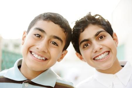 hombre arabe: Dos mejores amigos riendo ampliamente al aire libre Foto de archivo