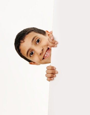 child holding sign: Portrait of a happy little boy holding a blank board against white background