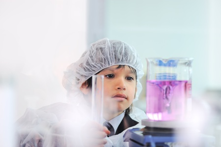 Smart cute little male child  experimenting with test tubes in real modern hospital lab photo