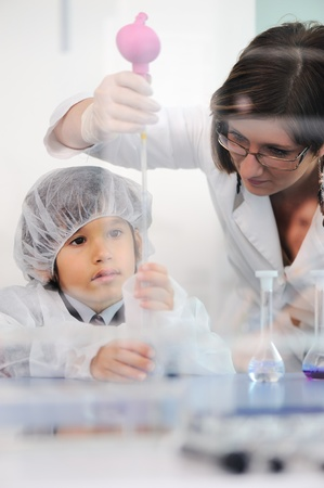 Smart cute little male child  experimenting in lab with his mother doctor scientist photo