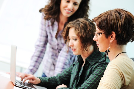 Group of young happy people looking into laptop working on it Stock Photo - 10585736