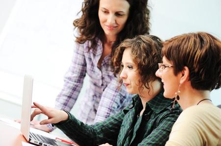 mujeres trabajando: En una reunión, un grupo de mujeres jóvenes que trabajan juntos en la mesa