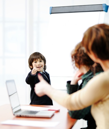 Genius kid on business presentation speaking to adults and giving them a lecture Stock Photo - 10585700