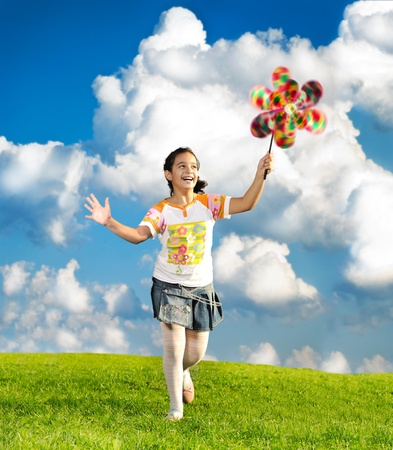 Fantastic scene of happy little girl running and playing carefreely on green meadow in nature photo