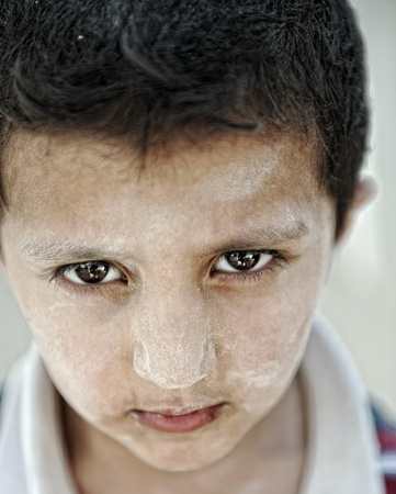 Portrait of poverty, little boy with strong look photo