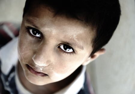 Portrait of poverty, little boy with sad eyes photo