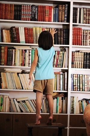 education choice: Kid trying to reach a book in the library Stock Photo