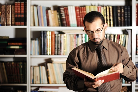 professors: Young man reading book in library Stock Photo