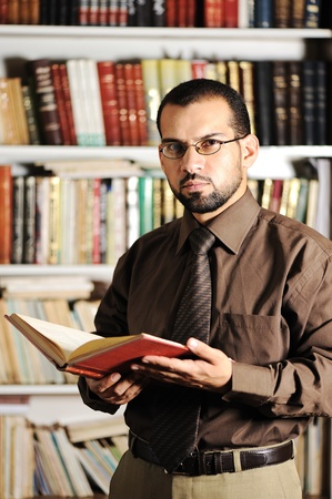 Young man reading book in library photo