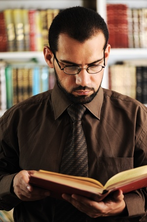 university professor: Young man reading book in library Stock Photo