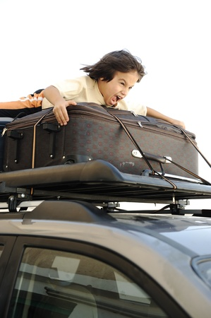Little boy traveling on bags, the top of the car photo