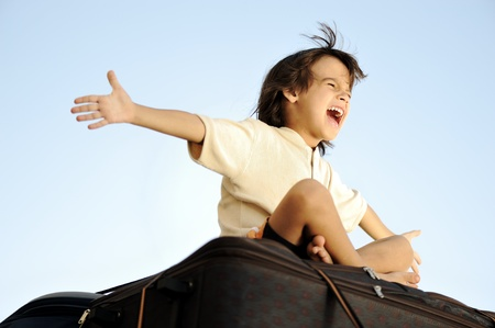 arms wide: Little boy traveling on bags, the top of the car