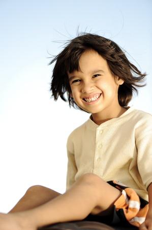 Happy summer boy sitting, wind in hair photo