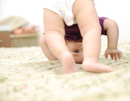 Baby boy playing upside down in bedroom photo