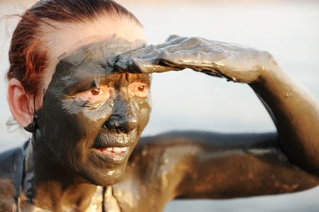 far away look: Elderly woman in a bathing suit of natural mineral mud sourced from the dead sea in Jordan