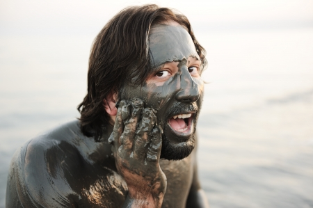 Man in a bathing suit of natural mineral mud sourced from the dead sea in Jordan photo