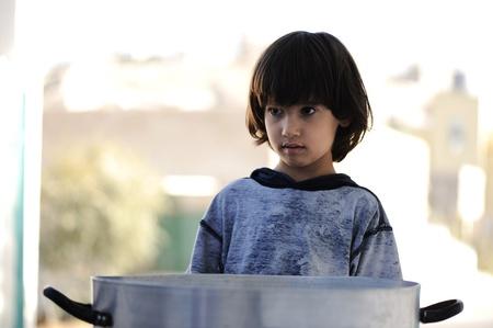 Portrait of poverty, little boy with sad eyes photo