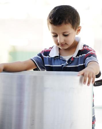 Portrait of poverty, little poor boy on food pot photo