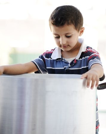 Portrait of poverty, little poor boy on food pot photo