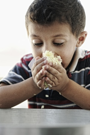despaired: Portrait of poverty, little poor boy on food pot eating rice