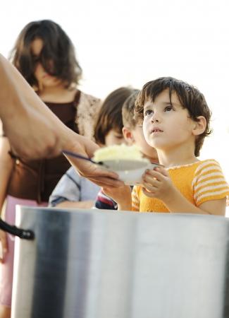 vagabundos: Niños hambrientos en campamento de refugiados, distribución de alimentos humanitaria Foto de archivo