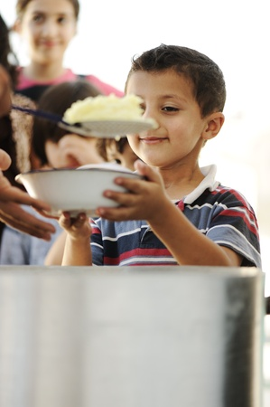 poor children: Hungry children in refugee camp, distribution of humanitarian food Stock Photo