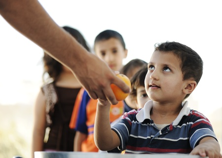 food distribution: Hungry children in refugee camp, distribution of humanitarian food Stock Photo