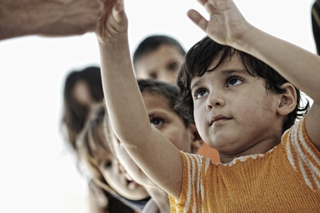 Hungry children in refugee camp, distribution of humanitarian food photo