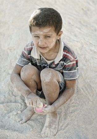 Portrait of poverty, little poor dirty boy in sand photo