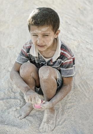 wees: Portret van de armoede, weinig slechte vieze jongen in het zand