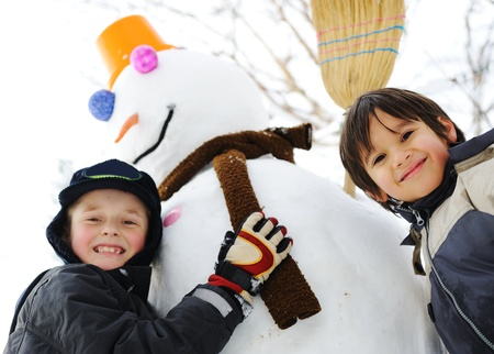Children on snow with snowman Stock Photo - 10680537