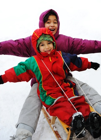 Boy and girl sledging on snow, happiness for brother and sister photo