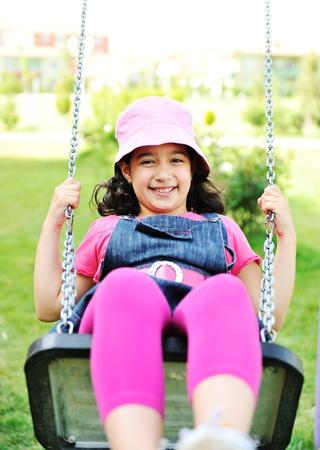 girl on swing: Little girl swinging in park