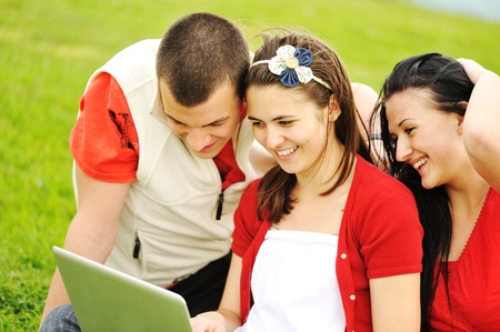 Teenage group with laptop on beautiful meadow photo