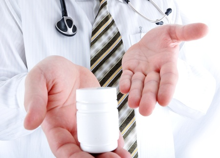Closeup, doctor holding little pills bottle - copy space for you photo