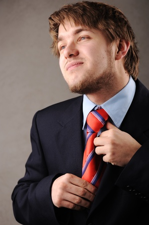 enticement: Young man with suit having problem with his tie