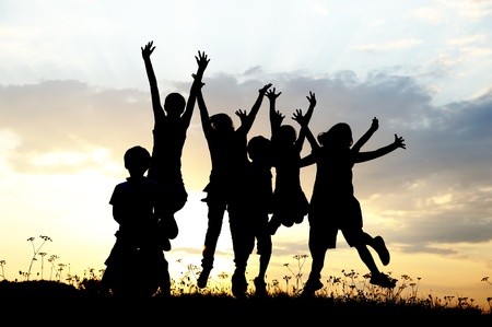 Silhouette, group of happy children playing on meadow, sunset, summertime photo