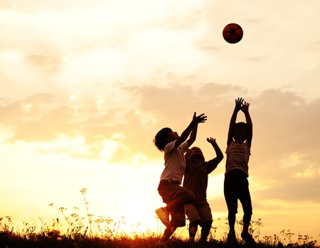 child sport: Silhouette, group of happy children playing on meadow, sunset, summertime