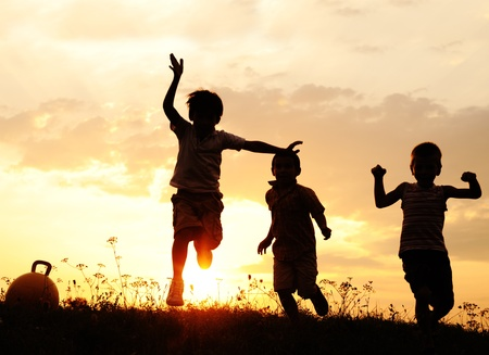 Silhouette, group of happy children playing on meadow, sunset, summertime Stock Photo - 10873832