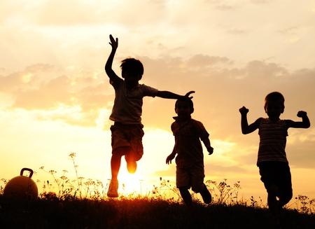 Silueta, grupo de niños felices jugando en la pradera, puesta del sol, verano