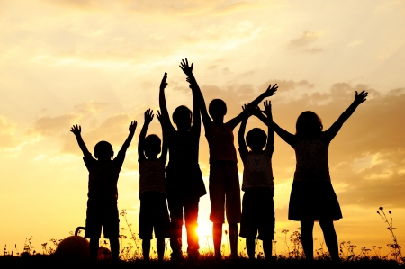 Silhouette, group of happy children playing on meadow, sunset, summertime Stock Photo - 10873858