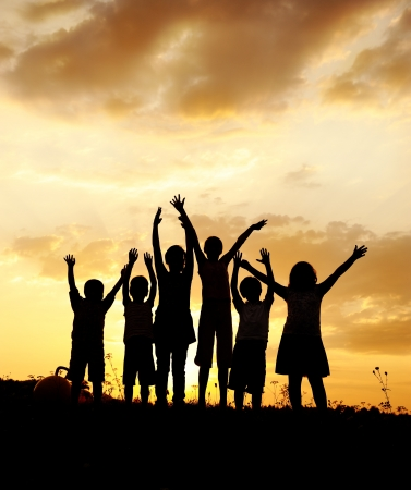Silhouette, group of happy children playing on meadow, sunset, summertime Stock Photo - 10873938