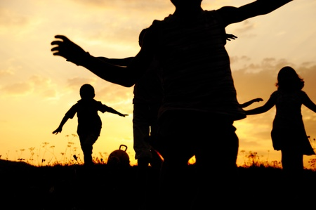 Silhouette, group of happy children playing on meadow, sunset, summertime Stock Photo - 10873795