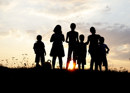Silhouette, group of happy children playing on meadow, sunset, summertime Stock Photo - 10873932