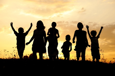Silhouette, group of happy children playing on meadow, sunset, summertime Stock Photo - 10873898