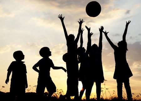 niños felices: Silueta, grupo de niños felices jugando en la pradera, puesta de sol, verano